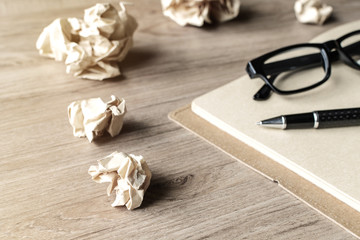 Crumpled paper balls with eye glasses and notebook on wooden des