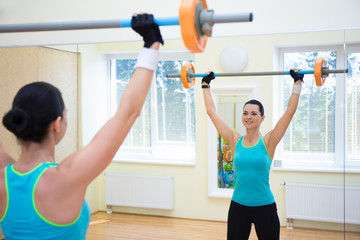 sport concept - young woman exercising with barbell