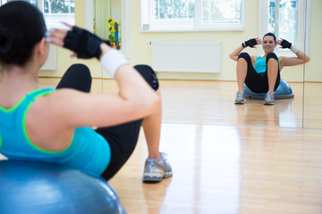young sporty woman doing exercises on bosu ball