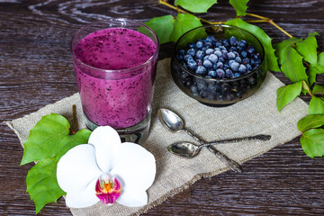 Blueberry smoothie on dark wooden background, still life