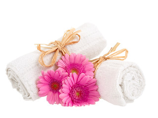 Rolled-up towels with flowers isolated on white background