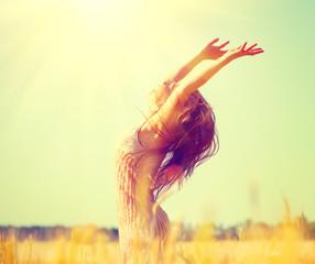 Beauty girl outdoors enjoying nature on wheat field