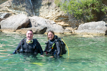Two Scuba Divers in shallow water before a dive