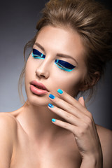 Beautiful girl with bright creative fashion makeup and blue nail