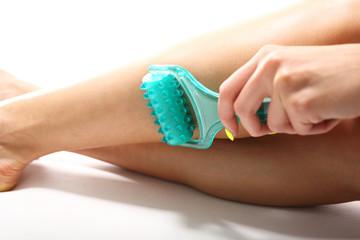 Fototapeta Masaż łydki.  Kobieca noga  podczas zabiegu masażu rolką kosmetyczną.