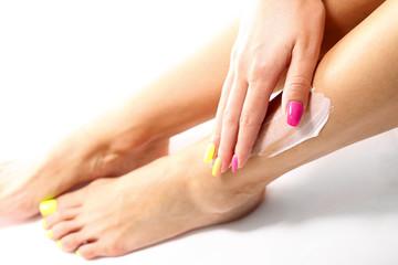 Depilacja nóg woskiem. Kobieta depiluje nogi plastrem z woskiem