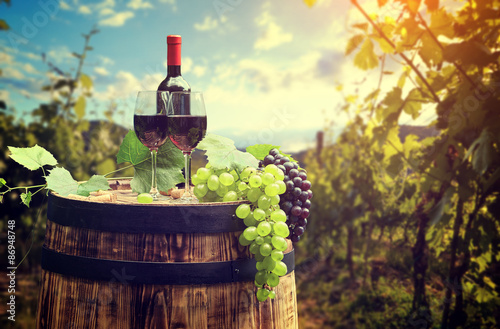Wall mural Red wine bottle and wine glass on wodden barrel. Beautiful Tusca