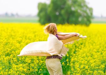 The beautiful woman dances on a rape field