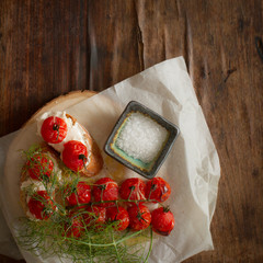 baked tomatoes with bread and dill on a wooden table