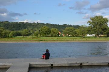 Junge Frau sitzt auf Bootsteeg