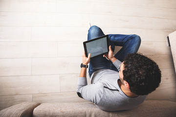 Young man sitting on floor and using tablet.