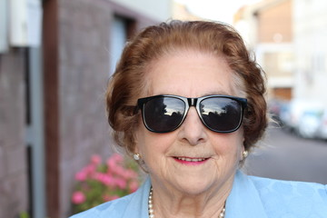 Portrait of a senior woman smiling and wearing sunglasses