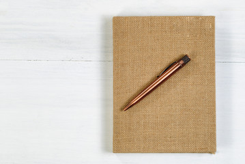 Vintage metal pen and burlap covered notepad on white desktop