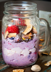 Healthy breakfast smoothie milkshake made from blended kefir yoghurt and topped with fresh berries, coconut shavings, chia seeds, pumpkin seeds and a whole strawberry.