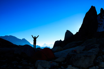 Silhouette of a person enjoying the sunrise in the mountains. Sports en lifestyle concept.