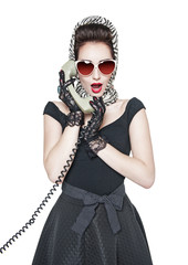 Surprised beautiful woman in pin-up style with retro telephone