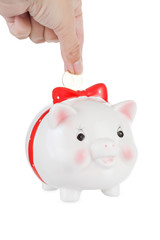 hand lowers a coin in a pig moneybox, is isolated on a white background