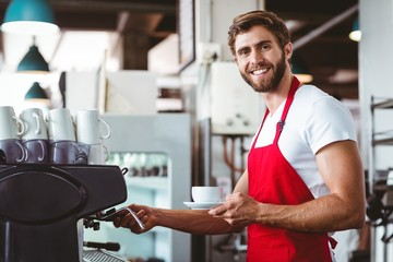 Handsome barista preparing a cup of coffee
