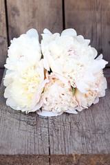 Splendid white pink peonies flowers on wooden planks