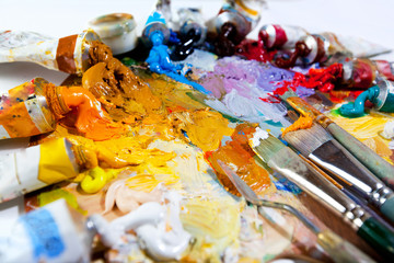 Art palette with oil paints and brushes.