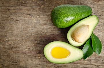 fresh avocado and  avocado like a bowl for oil on wooden backgro