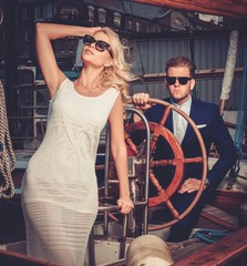 Stylish wealthy couple on a luxury yacht