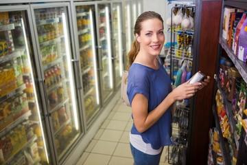 Happy pretty woman taking a product on shelf