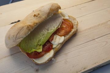 Panino con insalata mozzarella e pomodoro su piano di legno