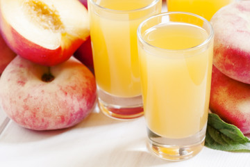 Fresh peach juice with fruits on a white wooden background, sele