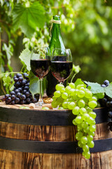 Wall Mural - Old wooden barrel with bottle and glass of red wine.