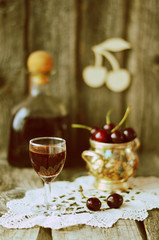 Cherry liquor in the little glasses and big bottle on the old wooden background with sepia effect