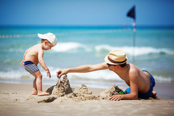 father and son build sand castle