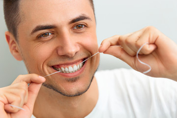 Closeup of young man flossing his teeth. Cleaning teeth with den