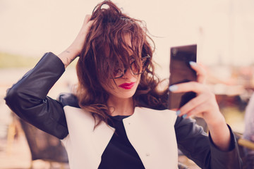 Woman fixing her hair, and take a self portrait with her smart phone