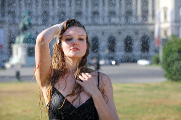 Young woman takes a refreshment under a sprinkler on a hot summer day