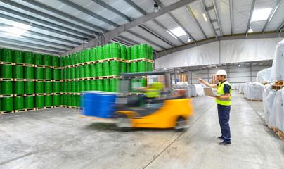 Arbeiter und Gabelstapler in einer Lagerhalle für Chemikalien // forklift and workers - shipping in a warehouse