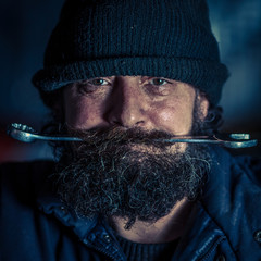 Portrait of mechanic with beard holding steel wrench in mouth