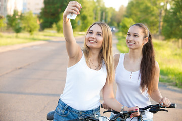 Smiling teenage girls taking self portrait with mobile phone