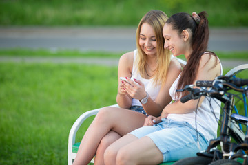 Cheerful teenage girls playing with cellphone on bench