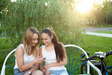 Cheerful teenage girls with cellphone in park