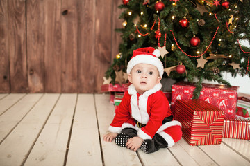 Baby in santa suit with gifts near xmas tree