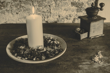 Candle on the wooden plate with coffee mill