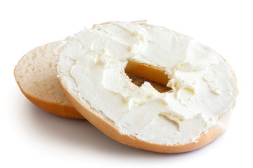 Plain bagel cut in half and spread with cream cheese. Isolated on white.