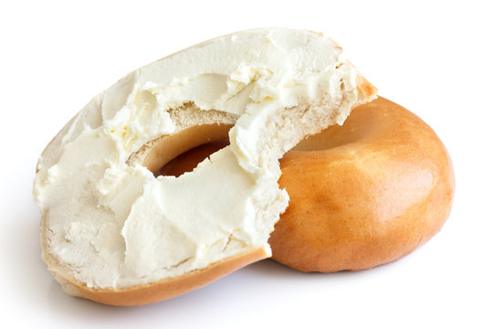 Plain bagel spread with cream cheese and bite missing. Isolated.