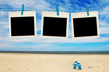 blank instant photos hanging on clothesline at the beach