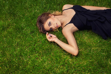 Beautiful sexy woman in black dress laying on the grass