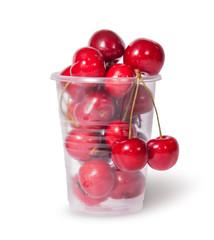 Red juicy sweet cherries in a plastic cup