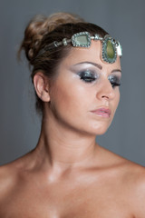 Blonde beautiful girl with smokey eyes makeup and a crown of jewels