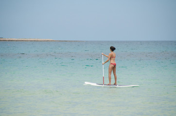 Girl paddling out on paddle board