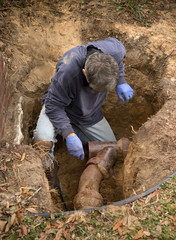 Man Examining Old Clay Ceramic Pipe Sewer Line in Hole in Ground